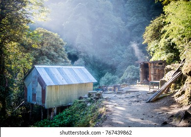 Sun rays on an old hut in forest on annapurna trekking circuit, Himalaya, Nepal