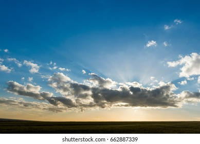 Sun rays peeking out above an attractive cloud formation during the golden hour
