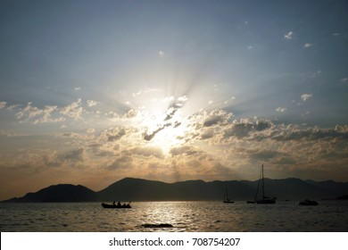 Sun rays seeping through the clouds at sunset time by the ocean in Liguria