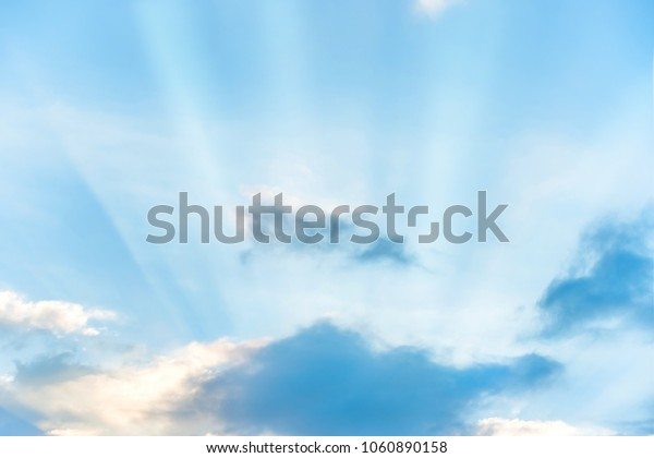 Sun rays shining through cloud on blue sunset sky