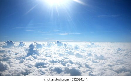 Sun rays shinning in the blue sky with layer of clouds viewed from above.