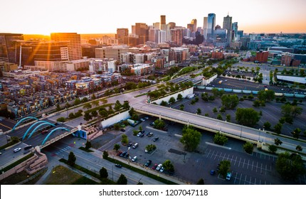 Sun rays star burst above Denver Colorado sunrise , golden hour sun rays across downtown skyline cityscape famous location in the mile high city , morning summer 2018 aerial drone view