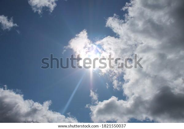 sun rays through blue clouded sky