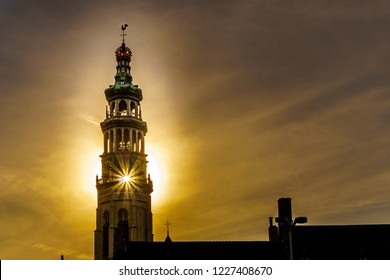Sun rays through the Lange Jan Toren (Long John Tower) of the medieval Abbey from the Sun setting behind the tower  in the Historic City of Middelburg in Zeeland Province, the Netherlands