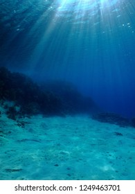 Sun rays and underwater landscape with sand. Seascape with sun beams and sandy seabed. Sun below the water surface.
