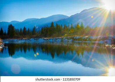Sun reflection in the water of the Columbia River in Fairmont Hot Springs, British Columbia. Purcell Mountains at sunset