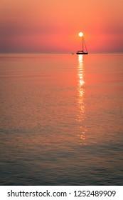 sun resting on a boat mast in coral sunrise