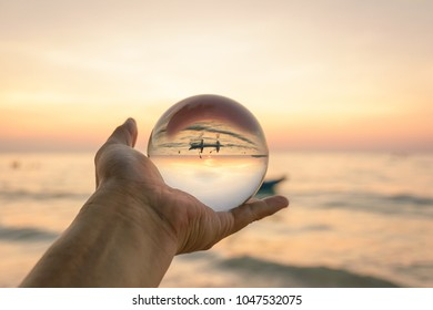 Sun rise on hand in the glass ball