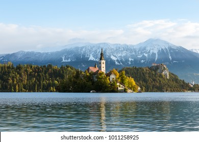 The sun rises above Lake Bled on a clear day. The mountains are visible behind the church on the island at Lake Bled.