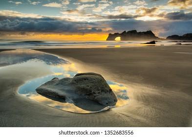 Sun rises behind Archway Islands, Wharariki Beach, Golden Bay, NZ