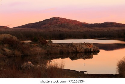 The sun rises casting beautiful shadows, reflections and a soft glow over the Plateaus and Lakes of the Wichita Mountains Wildlife Refuge located in Indiahoma, Oklahoma 2017
