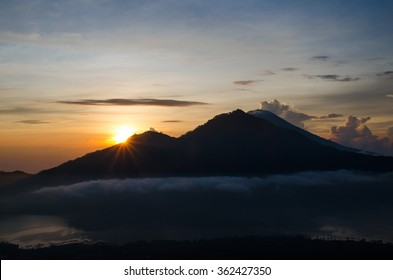 The sun rises at dawn from behind the mountains of Bali. Batur Volcano. Indonesia. Stock image.