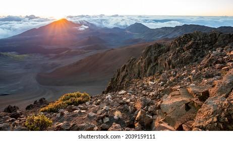 The sun rises dramatically over the dormant volcano and jagged peaks of Haleakala National Park on the island of Maui, Hawaii.
