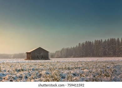 The sun rises late on a winter morning at the Northern Finland. The sunlight colors the snow covered fields and barns amber.