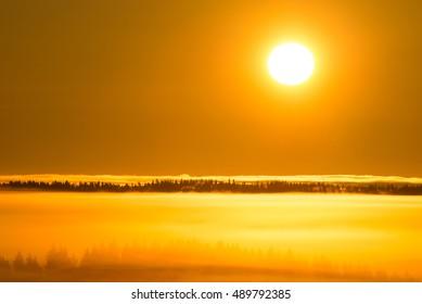 Sun rises in misty landscape