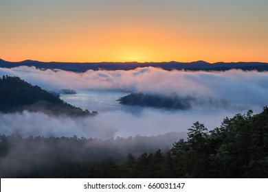 The sun rises on a foggy morning at Broken Bow Lake in Oklahoma, USA.