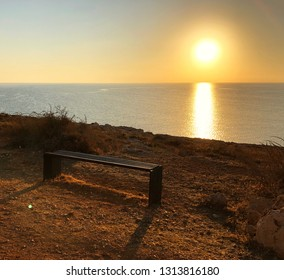 the sun rises on the horizon, where the sky merges with the sea, at the top of the rocky shore is a brown wooden bench for rest, planned sultry clear summer day