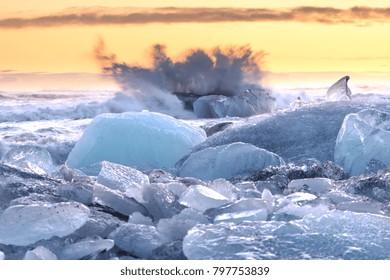 The sun rises over the Atlantic Ocean illuminating the famous Icebergs on Diamond Beach, at the opening of Jokulsarlon glacier lagoon