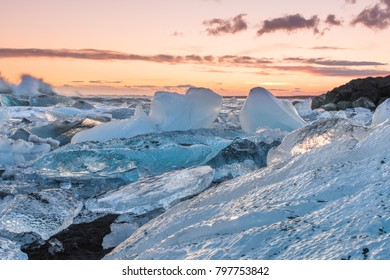 The sun rises over the Atlantic Ocean illuminating the famous Icebergs on Diamond Beach, at the opening of Jokulsarlon glacier lagoon