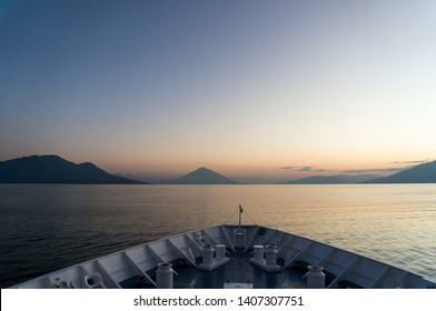 The sun rises over a calm Selat Flores, or Flores Strait. The strato-volcanoes show its position on the Pacific Ring of Fire