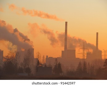 the sun rises over the coal power plant