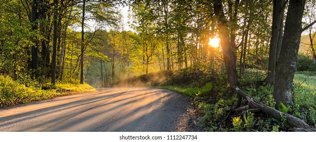 The sun rises over a dirt road in Vermont in the early springtime.