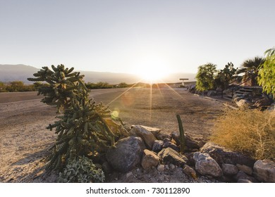 The sun rises over a gas station surrounded by cactus and an open road in Death Valley.