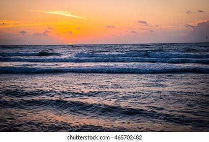 Sun RIses over gulf of mexico as waves crash on the beach on Padre Island , Texas near Corpus Christi