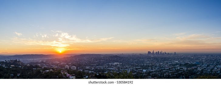 The sun rises over the horizon to the east of Los Angeles and a new day begins.