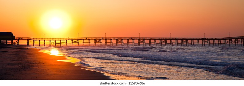 The sun rises over the pier at North Myrtle Beach, South Carolina. Creating gorgeous bright colors.