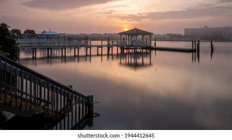 The sun rises over a private dock on Harbor Island while the buildings of Lumina Avenue are still obscured by morning mist. Space for copy