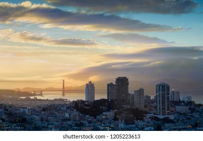 The sun rises over San Francisco, California. Night lighting illuminates Russian Hill while the Golden Gate Bridge receives first sun light.