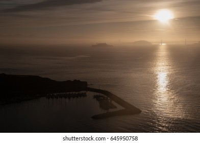 Sun rises over San Francisco Bay Bridge with Alcatraz and Angel Island, and Sausalito harbor in foreground.