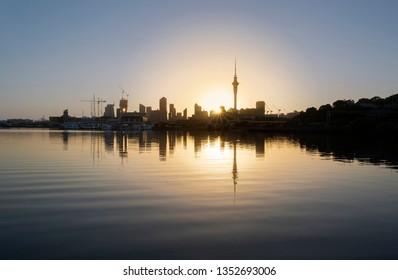 Sun rises over Sky Tower & Auckland city skyline, New Zealand