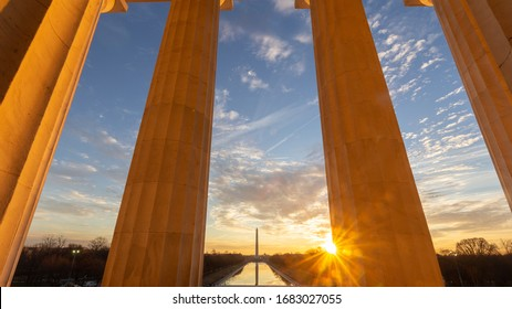 The sun rises over Washington, D.C. and the Lincoln Memorial Reflecting Pool as seen from inside the Lincoln Memorial and it's stone pillars