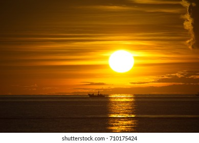 The sun rises from the sea with soft light, slowly at every step, with a beautiful beam.