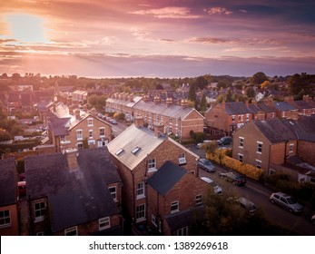Sun rising above a traditional British housing estate with countryside in the background. Very typically English houses that are over 100 years old.