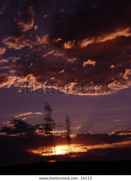 Sun rising behind clouds and powerlines.