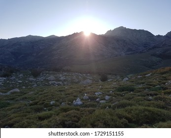 Sun rising from behind a mountain on the GR20 trail in Corsica