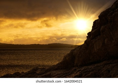 The sun rising behind the rocks in the lake, Spain