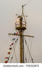 The sun is rising behind a ship's crows nest on the Columbia River, Astoria, Oregon on a foggy riverfront morning.
