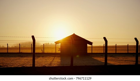 Sun rising behind a small shed in a frost covered field