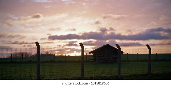Sun rising behind a wooden shed in a field