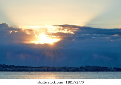 Sun rising from black clouds above the city by the sea in Spain