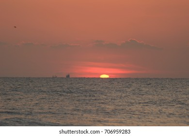 sun rising with fisherman boat passing by off shore Pranburi beach Thailand