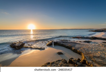 Sun is rising at the horizon and lit sand beaches of Formentera island. Spain.
