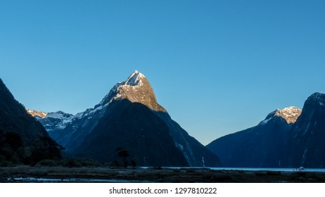 the sun rising on the summit of mitre peak at milford sound in new zealand