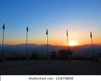 Sun rising over Andalusian hills behind flag poles on still day