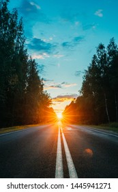 Sun Rising Over Asphalt Country Open Road In Sunny Morning Or Evening. Open Free Road In Summer Or Autumn Season At Sunny Sunset Or Sunrise Time