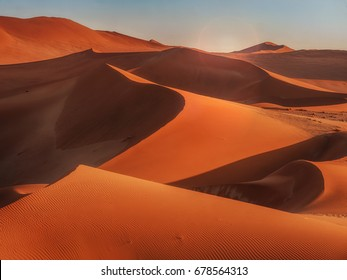 Sun rising over the curves, lines, and shadows of the red sand dunes of Namib Desert, Namibia.